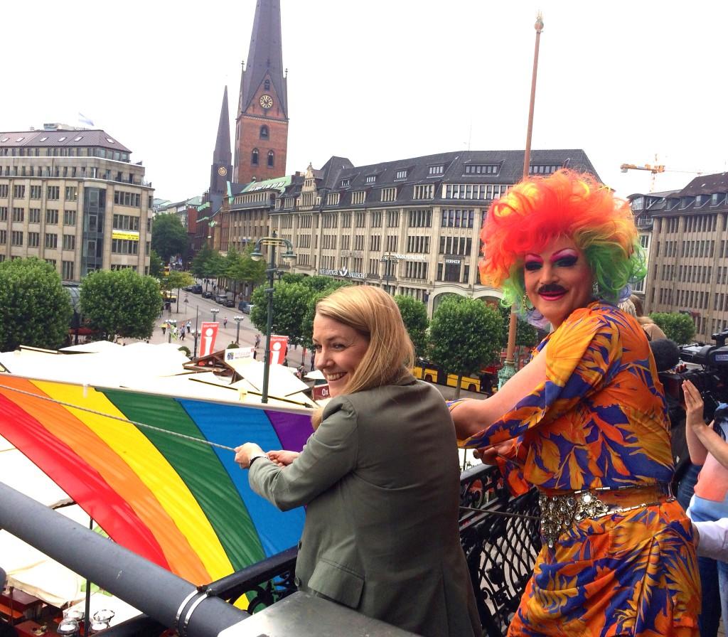 Referenz an Conchita Wurst – Olivia Jones mit Bart beim CSD-Flagge hissen vor dem Hamburger Rathaus